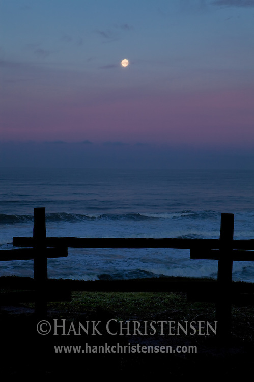 The moon sets behind off-shore fog, cast in a purple hue from the rising sun