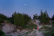 Woman taking the trail back to her campsite over the freshwater coastal dunes at The Pinery Provincial Park on Lake Huron near Grand Bend, Ontario, Canada.