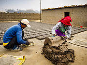 09 MARCH 2017 - BAGMATI, NEPAL: Workers put clay into brick molds at a brick factory in Bagmati, near Bhaktapur. The live in the building in the background. There are almost 50 brick factories in the valley near Bagmati. The brick makers are very busy making bricks for the reconstruction of Kathmandu, Bhaktapur and other cities in the Kathmandu valley that were badly damaged by the 2015 Nepal Earthquake. The brick factories have been in the Bagmati area for centuries because the local clay is a popular raw material for the bricks. Most of the workers in the brick factories are migrant workers from southern Nepal.           PHOTO BY JACK KURTZ