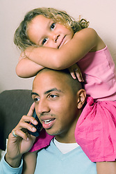Father on the telephone being cuddled by his daughter,