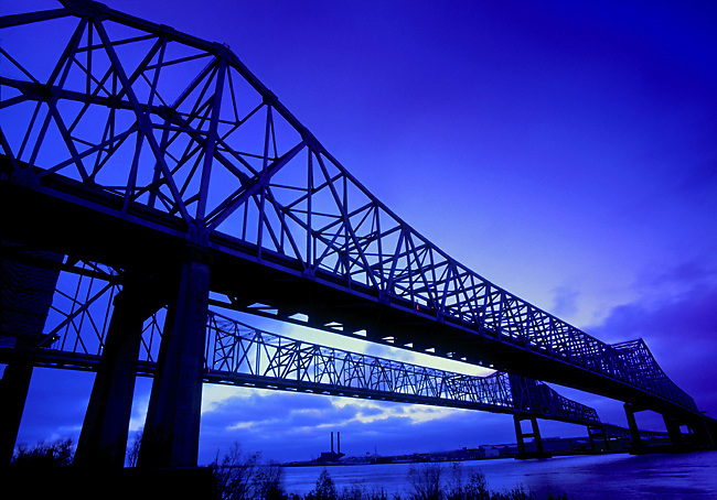A blue dawn arrives over the double span of the Greater New Orleans Bridge, also referred to as the Crescent City Connection.  The bridge crosses the Mississippi River from east to west.