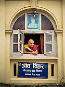 01 AUGUST 2015 - KATHMANDU, NEPAL: A Buddhist monk looks out the window of his monastery near Shree Gha stupa in Kathmandu.      PHOTO BY JACK KURTZ