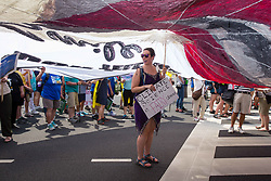 April 29, 2017 - Washington, D.C, U.S - A protestor stood under a huge banner as she joined over 200,000 others from across the country, to participate in a People's Climate March on Trump's 100th day in office.  Braving 90 degree heat, protestors marched along Pennsylvania Avenue, chanting ''water is life'' and ''keep it in the soil, can't drink oil! (Credit Image: © Nancy Siesel via ZUMA Wire)