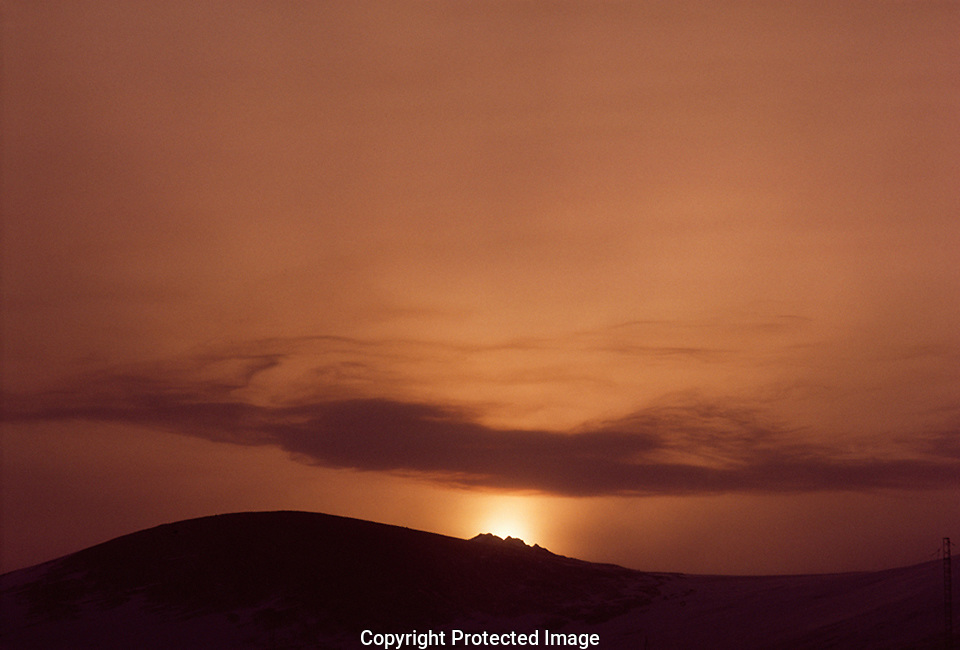 antarctic sunset dropping behind a hill