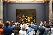 Visitors in a tour group view famous painting by Rembrandt 'The Night Watch' at Rijksmuseum in Amsterdam, Holland