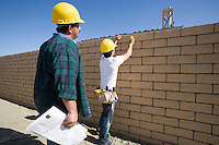 Construction workers standing in front of brick wall