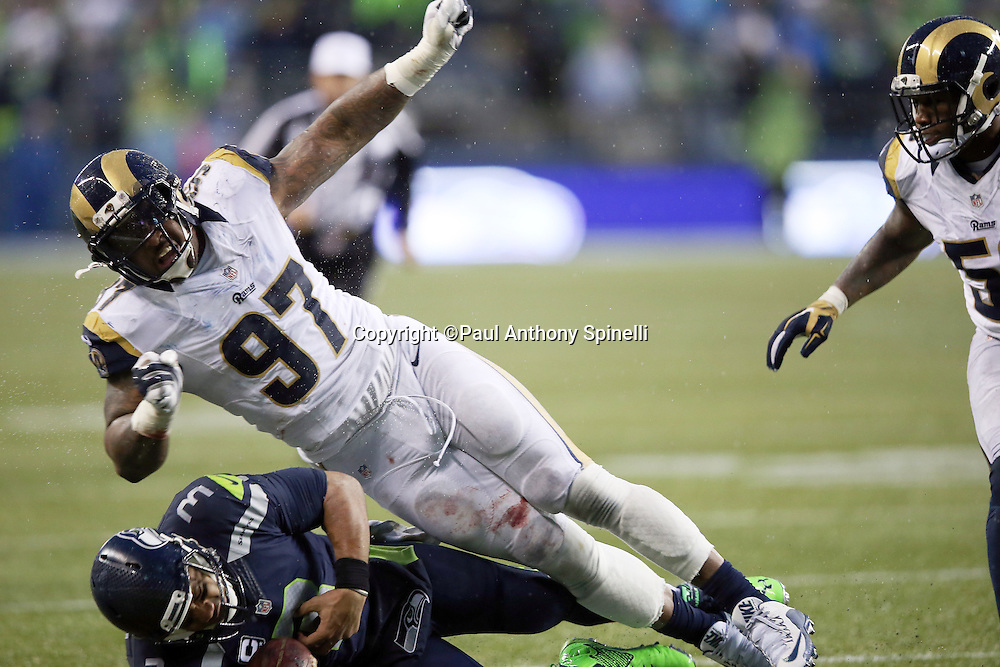 St. Louis Rams defensive end Eugene Sims (97) hits Seattle Seahawks quarterback Russell Wilson (3) and causes a fumble recovered by St. Louis Rams outside linebacker Akeem Ayers (56) and stopping a potential scoring drive and stifling a Seahawks comeback attempt late in the fourth quarter during the 2015 NFL week 16 regular season football game against the Seattle Seahawks on Sunday, Dec. 27, 2015 in Seattle. The Rams won the game 23-17. (©Paul Anthony Spinelli)