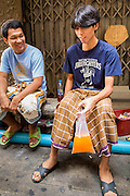 "11 JANUARY 2013 - BANGKOK, THAILAND:    Muslim teenagers share an orange soda soft drink in the Ban Krua neighborhood in Bangkok. The Ban Krua neighborhood of Bangkok is the oldest Muslim community in Bangkok. Ban Krua was originally settled by Cham Muslims from Cambodia and Vietnam who fought on the side of the Thai King Rama I. They were given a royal grant of land east of what was then the Thai capitol at the end of the 18th century in return for their military service. The Cham Muslims were originally weavers and what is known as ""Thai Silk"" was developed by the people in Ban Krua. Several families in the neighborhood still weave in their homes.                  PHOTO BY JACK KURTZ"