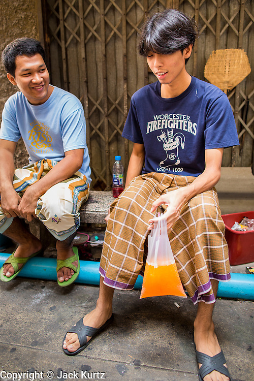 """11 JANUARY 2013 - BANGKOK, THAILAND:    Muslim teenagers share an orange soda soft drink in the Ban Krua neighborhood in Bangkok. The Ban Krua neighborhood of Bangkok is the oldest Muslim community in Bangkok. Ban Krua was originally settled by Cham Muslims from Cambodia and Vietnam who fought on the side of the Thai King Rama I. They were given a royal grant of land east of what was then the Thai capitol at the end of the 18th century in return for their military service. The Cham Muslims were originally weavers and what is known as """"Thai Silk"""" was developed by the people in Ban Krua. Several families in the neighborhood still weave in their homes.                  PHOTO BY JACK KURTZ"""