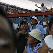 THE PHILIPPINES (Manila). 2009. Gamblers make wagers with each other as they bet on the cockfighting at the La Loma, La Loma, Manila. Photo Tim Clayton <br /> <br /> Cockfighting, or Sabong as it is know in the Philippines is big business, a multi billion dollar industry, overshadowing Basketball as the number one sport in the country. It is estimated over 5 million Roosters will fight in the smalltime pits and full-blown arenas in a calendar year. TV stations are devoted to the sport where fights can be seen every night of the week while The Philippine economy benefits by more than $1 billion a year from breeding farms employment, selling feed and drugs and of course betting on the fights...As one of the worlds oldest spectator sports dating back 6000 years in Persia (now Iran) and first mentioned in fourth century Greek Texts. It is still practiced in many countries today, particularly in south and Central America and parts of Asia. Cockfighting is now illegal in the USA after Louisiana becoming the final state to outlaw cockfighting in August this year. This has led to an influx of American breeders into the Philippines with these breeders supplying most of the best fighting cocks, with prices for quality blood lines selling from PHP 8000 pesos (US $160) to as high as PHP 120,000 Pesos (US $2400)..