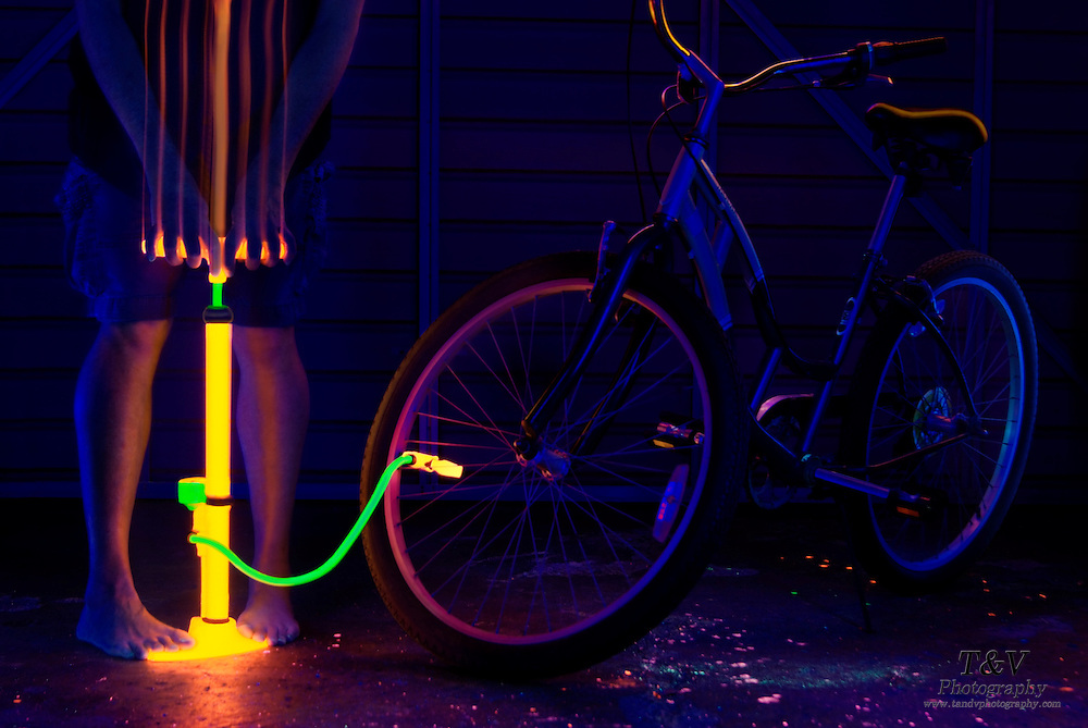 A bicycle tire is filled with air by a man using a glowing pump. Blacklight Photography