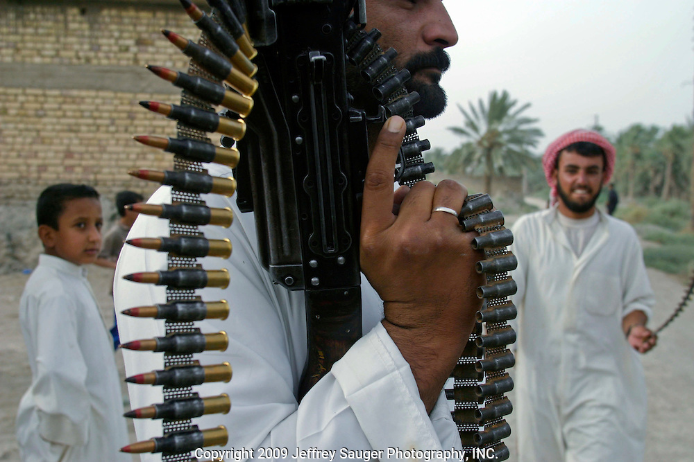 A member of the Al Hacham Tribe holds his Russian-made BKC machine gun as members of the extended Al-kasid family participate in  Hawaies, a traditional tribal Arabic dance, at the Al-kasid family's Istikbal, or homecoming, in their home village Suq ash Shuyukh about 20 miles southeast of Nasiriyah, Iraq, Tuesday, July 29, 2003.