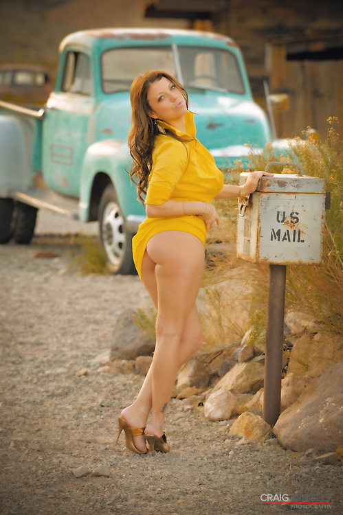 Beautiful brunette woman with old car & mailbox in desert