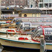 NLD/Amsterdam/201070410 - Rondvaartboten liggend aan de kade in Amsterdam
