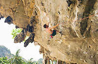 Man climbing overhanging limestone rock face on Tonsai Beach Southern Thailand&#xA;<br />