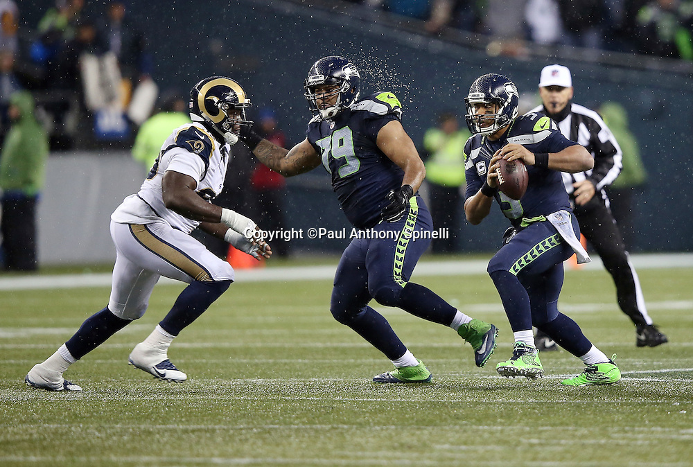 Seattle Seahawks quarterback Russell Wilson (3) gets a block on St. Louis Rams defensive end William Hayes (95) by Seattle Seahawks tackle Garry Gilliam (79) as he runs the ball with less than one minute left in the fourth quarter during the 2015 NFL week 16 regular season football game against the St. Louis Rams on Sunday, Dec. 27, 2015 in Seattle. The Rams won the game 23-17. (©Paul Anthony Spinelli)