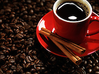 Red espresso cup of coffee on coffee beans background