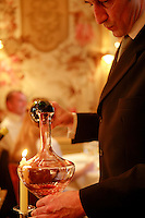 Sommelier decanting red wine at the restaurant l'Ambroisie in Paris' Place des Vosges