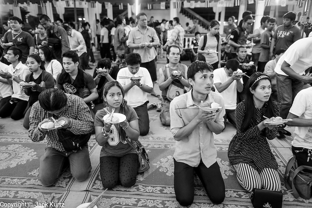 "15 MARCH 2014 - NAKHON CHAI SI, NAKHON PATHOM, THAILAND: People pray at the beginning of the Wat Bang Phra tattoo festival. Wat Bang Phra is the best known ""Sak Yant"" tattoo temple in Thailand. It's located in Nakhon Pathom province, about 40 miles from Bangkok. The tattoos are given with hollow stainless steel needles and are thought to possess magical powers of protection. The tattoos, which are given by Buddhist monks, are popular with soldiers, policeman and gangsters, people who generally live in harm's way. The tattoo must be activated to remain powerful and the annual Wai Khru Ceremony (tattoo festival) at the temple draws thousands of devotees who come to the temple to activate or renew the tattoos. People go into trance like states and then assume the personality of their tattoo, so people with tiger tattoos assume the personality of a tiger, people with monkey tattoos take on the personality of a monkey and so on. In recent years the tattoo festival has become popular with tourists who make the trip to Nakorn Pathom province to see a side of ""exotic"" Thailand.   PHOTO BY JACK KURTZ"