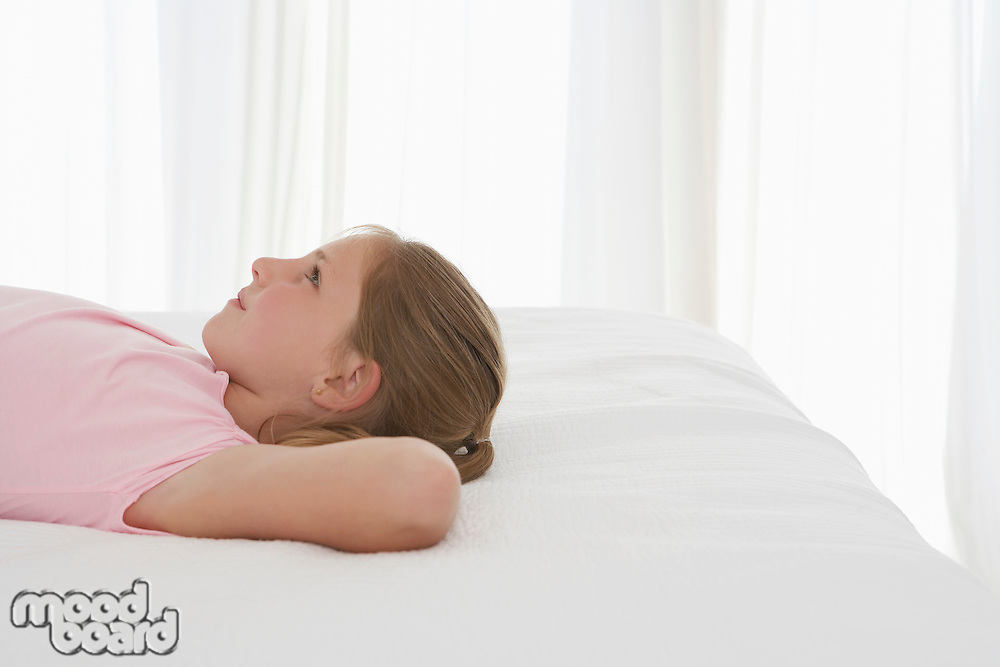 Girl lying on bed profile half-length