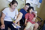 20 JUNE 2009 - PHOENIX, AZ: Mireya Renteria holds her son Ricardo while she helps another patient with some of the outreach literature in the walk in clinic at the Cultural Cup. The walk in clinic at the Cultural Cup Food Bank started two years ago when Cultural Cup founder Zarinah Awad wanted to expand the food bank's outreach and provide basic medical care for the people who use the food bank. The clinic sees, on average, 7 - 11 patients a week. Awad said that as the economy has worsened since the clinic opened and demand has steadily increased. She attributes the growth to people losing their jobs and health insurance. The clinic is staffed by volunteers both in the office and medical staff. Adults are seen every Saturday. Children are seen one Saturday a month, when a pediatrician comes in. Awad, a Moslem, said the food bank and clinic are rooted in the Moslem tradition of Zakat or Alms Giving, the giving of a small percentage of one's income to charity which is one of the Five Pillars of Islam.   PHOTO BY JACK KURTZ