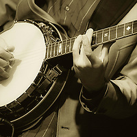 High contrast black and white with green tint.  Banjo player during live stage performance.