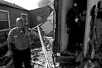 A police officer, left, along with emergency personnel find the remains of a elderly man still inside his home in the lower ninth ward over a month after hurricane katrina made lanfall 8 October 2005 New Orleans Louisiana.  (photo by Darren Hauck)