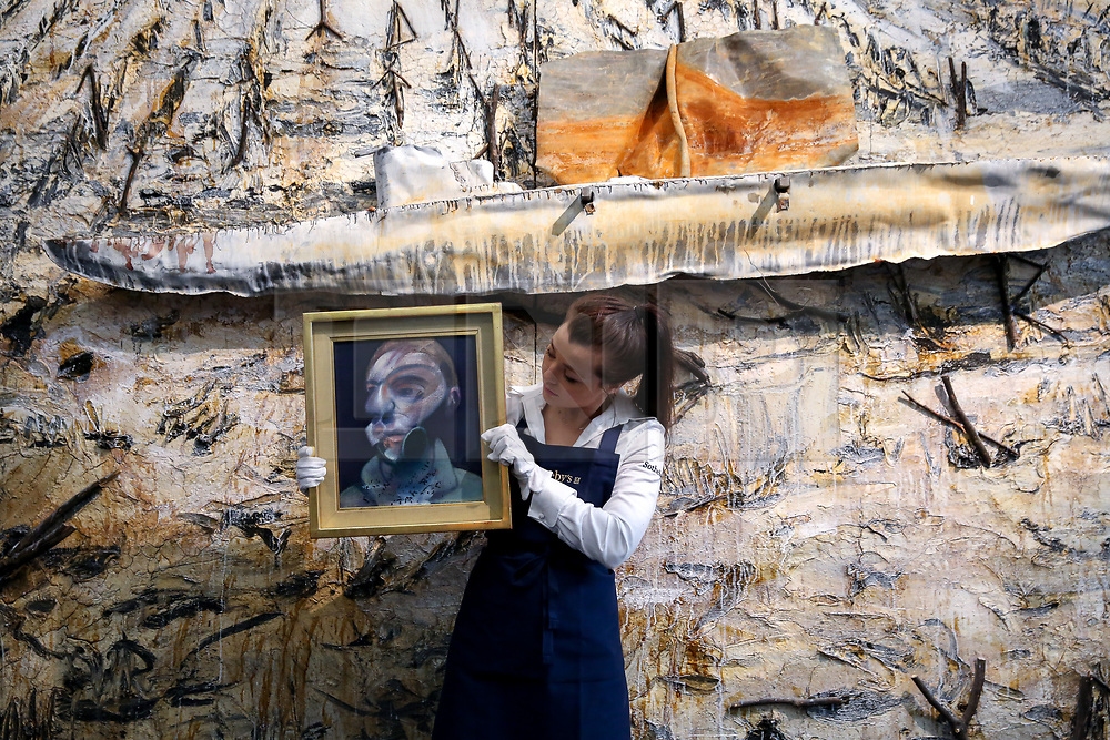 "© Licensed to London News Pictures. 21/06/2019. London, UK. A technician holds Francis Bacon's ""Self-Portrait"", 1975 (Est £15m- £20m) in front of in front of Anselm Kiefer's ""Des Herbstes Runengespinst (Est £800,00 - £1.2m) at the preview of Summer Contemporary Art Auctions at Sotheby's George Street, London. Photo credit: Dinendra Haria/LNP"