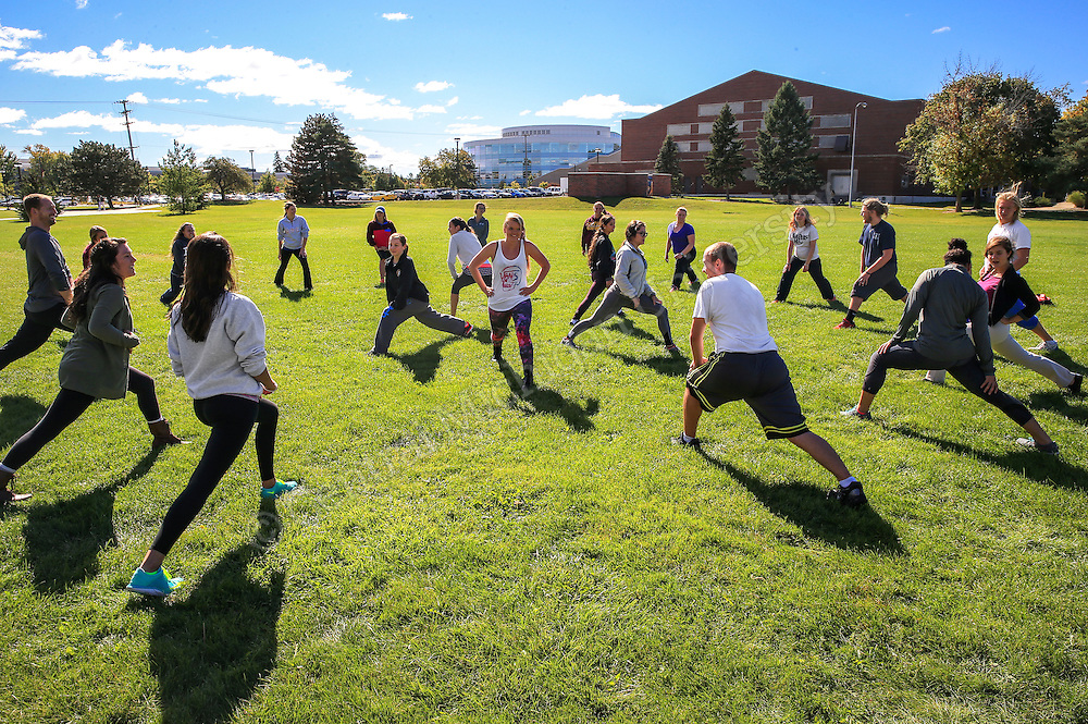 Tom Kozal, instructor of HSC 106HQR-Honors section.  Kozal joins students doing fitness exercises outside of the Health Professions building. Their topic for the week was Exercise for Health and Fitness. Each group of students were given a variety of topics such as cardio, upper body, lower body, and stretching.  They were to teach different components from their topic to the class.  Photo by Steve Jessmore/Central Michigan University