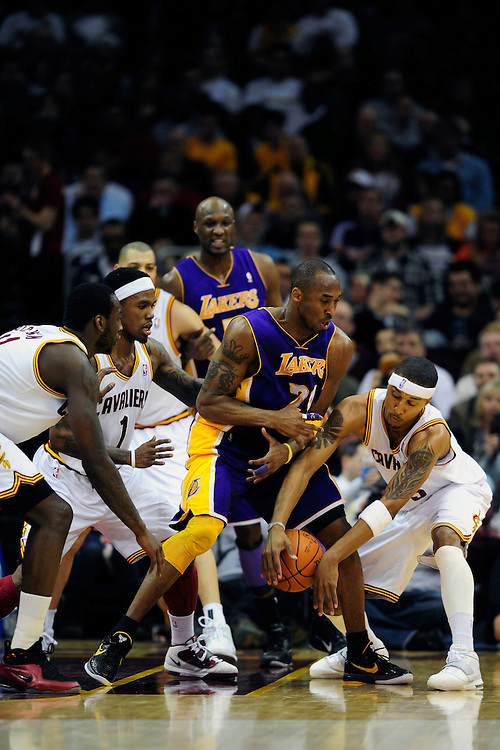 Feb. 16, 2011; Cleveland, OH, USA; Los Angeles Lakers shooting guard Kobe Bryant (24) looses the ball under pressure from Cleveland Cavaliers power forward J.J. Hickson (21) point guard Daniel Gibson (1) and small forward Jamario Moon (15) during the second quarter at Quicken Loans Arena. Mandatory Credit: Jason Miller-US PRESSWIRE