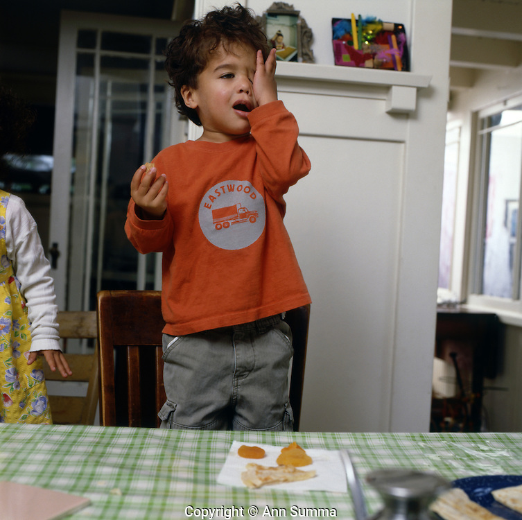 A boy is exasperated while eating a snack.