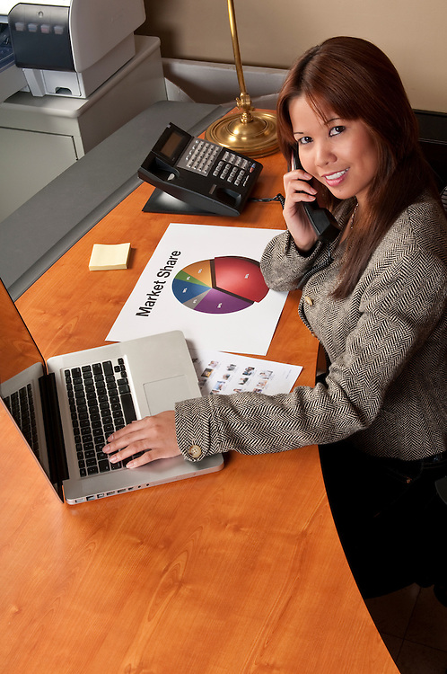Young woman talking by phone and working on computer in small office.