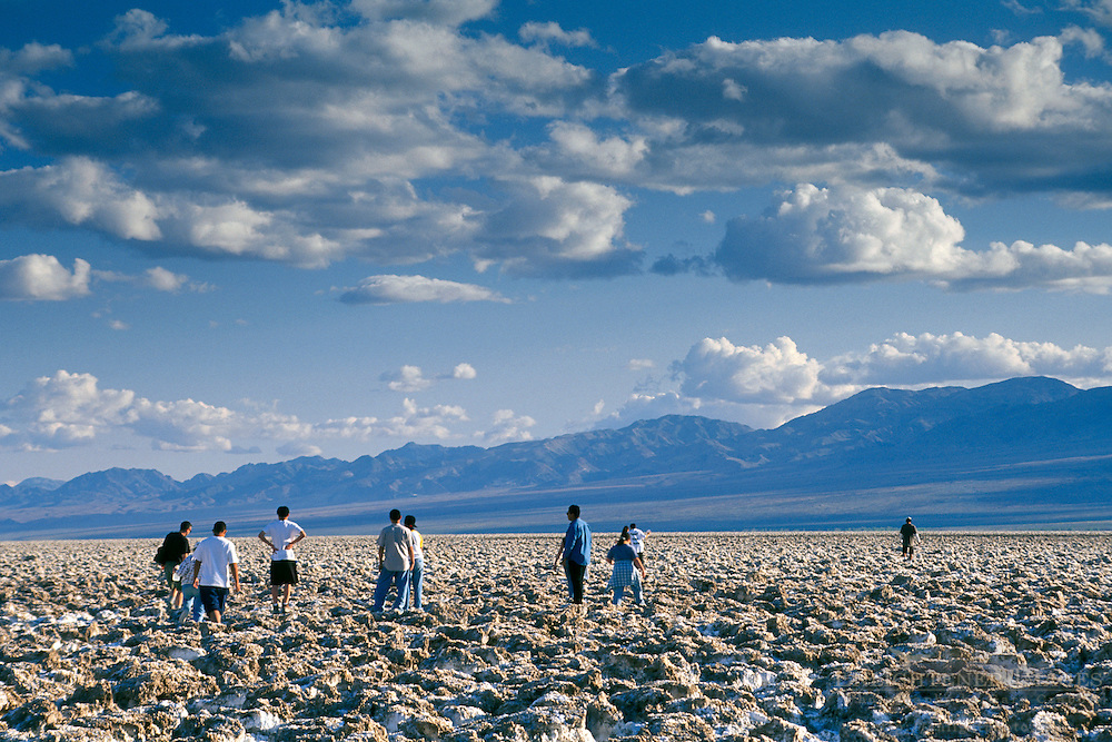 Tourists walking on salt encrusted rocks at Devlis, Golf Course, Death Valley National Park, California