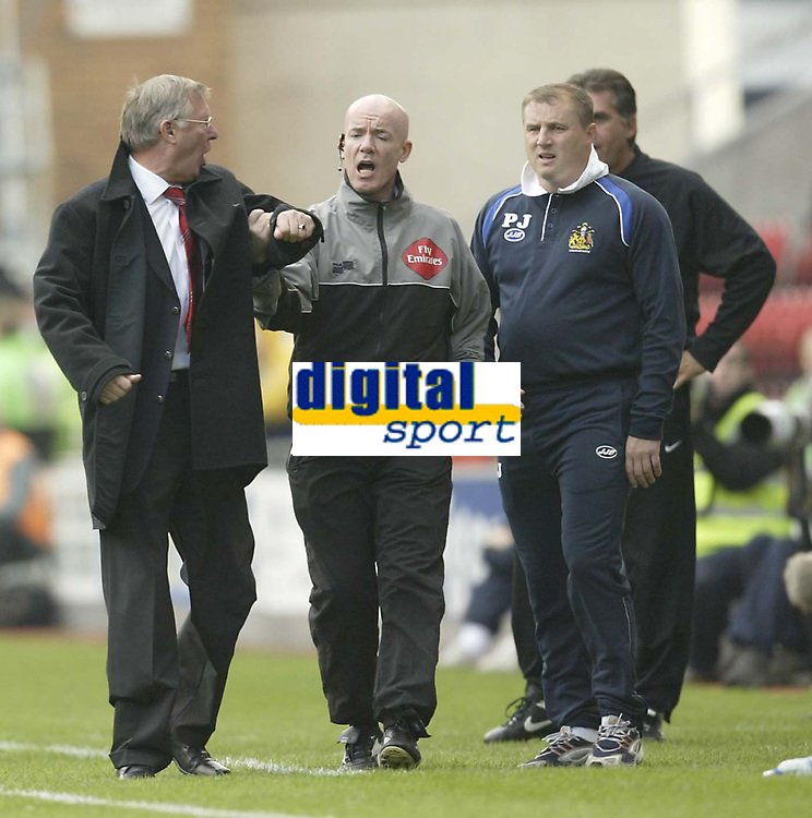 Photo: Aidan Ellis.<br /> Wigan Athletic v Manchester United. The Barclays Premiership. 14/10/2006.<br /> the Fourth official pulls Alex Ferguson back after a poor decision from the referee