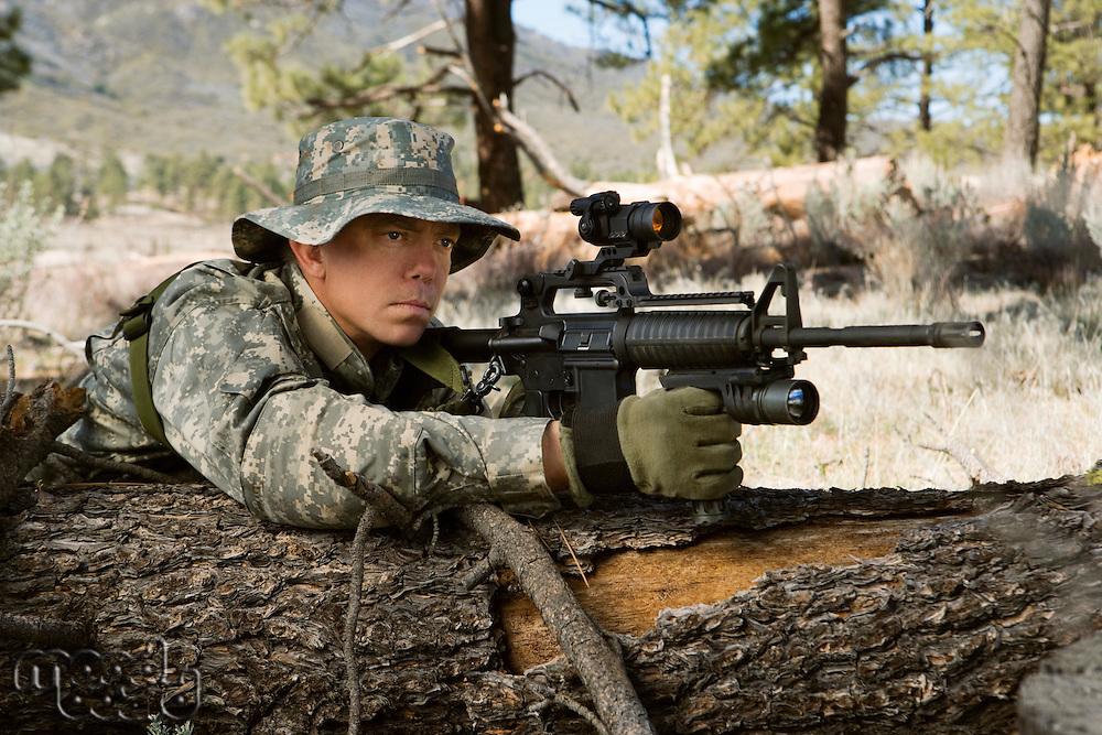 Soldier aiming machine gun, leaning on log