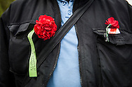 01/05/2015 – Berlin, Germany: The chest of a supporter of DGB, the Confederation of German Trade Unions,  with a red flower and a pin during the speech in front of the Brandenburg gate to celebrate the International Workers Day. The International Workers Day is a celebration of laborers and the working classes that is promoted by the international labor movement, anarchists, socialists, and communists and occurs every year on May Day. (Eduardo Leal)