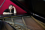 "Singer/song-writer, Kim Moberg, 58, is framed by the 102 year-old Steinway grand piano in her home in Centerville, MA. When Kim and her husband were trying to have a second child years ago, she discovered a lump. She was put on tamoxifen and had a lumpectomy and thought everything was fine. ""Soon after that my mom was diagnosed with breast cancer and died shortly after at the age of 63; then my younger sister was diagnosed at 41 and died after a long struggle with it,"" she explains. Kim got genetically tested and discovered the had the BRCA2 genetic mutation. Since it put her at extremely high risk of developing cancer, she knew she had to have a double mastectomy and ovary removal. ""My husband, Rob is my rock and he did everything during that time period after the surgeries so I could concentrate on getting better,"" she says. Kim, who was born in Alaska and whose mother is Native America (Tlingit), grew up surrounded by music. ""My mother was a classical pianist and taught me guitar when I was around 13 years-old,"" she recalls. ""I'm drawn to musical stories that tug at feelings of melancholy, heartbreak and healing,"" says Kim whose two daughters too have embraced music. While her younger daughter, Rebecca, is adopted, she knows her older daughter, Rachel, will too have to be genetically tested and potentially make decisions about risk factor health choices when she gets older."