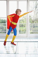 Young boy (7-9) wearing superhero costume arm extended side view