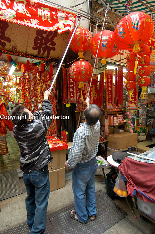 Shop keepers hang red lanterns outside shop during traditional Chinese Lunar New Year festival in Hong Kong