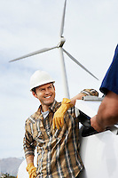 Engineers near wind turbine at wind farm