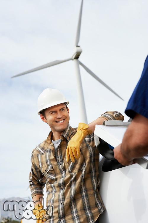 Engineers near wind turbine at wind farm