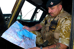 A British soldier, of the Light Infantry, serving with the Muliti National Division in beret and desert camouflage, sits in an army land rover while looking at a military map of the area around  Basra Air Station during Op Telic Iraq 2005