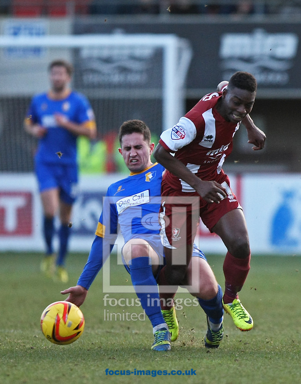 Picture by Mark Hawkins/Focus Images Ltd 07949 023795<br /> 29/12/2013<br /> Jermaine Mcglashan of Cheltenham Town is felled by Chris Clements of Mansfield Town during the Sky Bet League 2 match at the Abbey Business Stadium, Cheltenham.