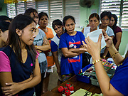 29 JANUARY 2018 - MALILIPOT, ALBAY, PHILIPPINES: Women in a shelter learn to make face masks to protect themselves and their families from volcanic ash. They live on the slopes of Mayon volcano and were evacuated when the volcano started erupting. Mayon volcano's eruptions continued Monday. At last count, more 80,000 people have been evacuated from their homes of the slopes of the volcano and are crowded into shelters in communities outside of the danger zone.    PHOTO BY JACK KURTZ