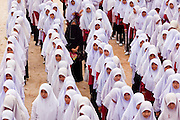 "Sept. 29, 2009 -- SAI BURI, THAILAND:  A teacher walks through a crowd of girls at a formation before classes at the Darunsat Wittya Islamic School in Sai Buri, Thailand. The school is the largest Muslim high school in Pattani province. Although it is a private school, the Thai government pays students' tuition to attend the school. The curriculum combines Thai official curriculum with Islamic curriculum. Many of the students go on to college level education in Egypt and Saudi Arabia. The Thai government views Islamic high schools with suspicion, fearing they radicalize students. Thailand's three southern most provinces; Yala, Pattani and Narathiwat are often called ""restive"" and a decades long Muslim insurgency has gained traction recently. Nearly 4,000 people have been killed since 2004. The three southern provinces are under emergency control and there are more than 60,000 Thai military, police and paramilitary militia forces trying to keep the peace battling insurgents who favor car bombs and assassination.   Photo by Jack Kurtz / ZUMA Press"