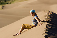 A female camper travels in The Great Sand Dunes National Park in summer  in the San Luis Valley of SW Colorado.