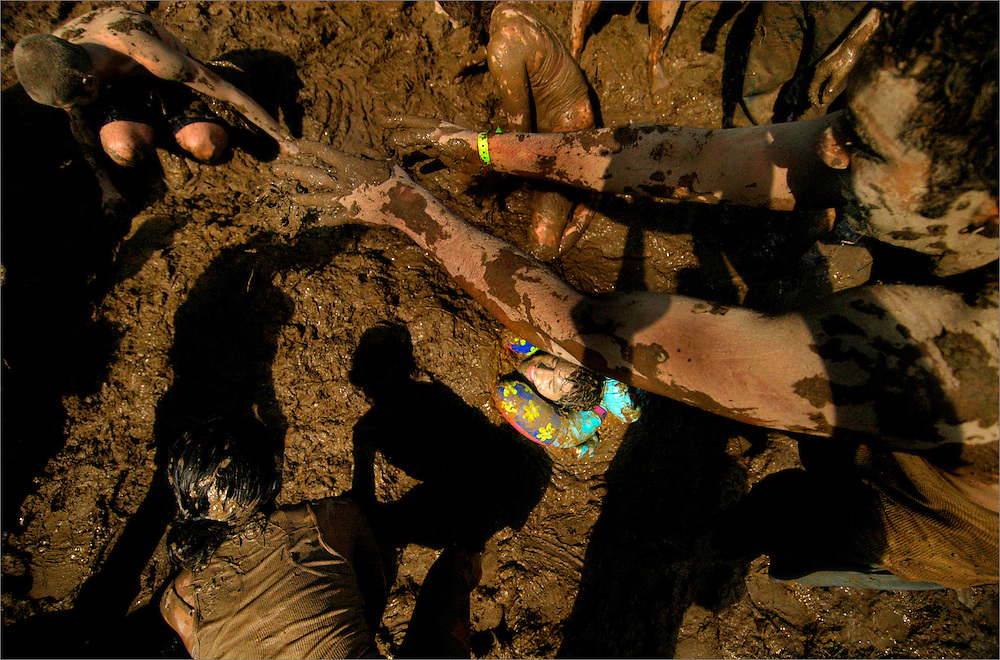 """Daniel Gordon lays in a mud-filled bed as his friends cover his entire body during the annual """"Mud Tug"""" at the Rochester Institute of Technology in Rochester, New York on September 18, 2004.  The annual event included food, drinks, tugs, and many random mud fights."""