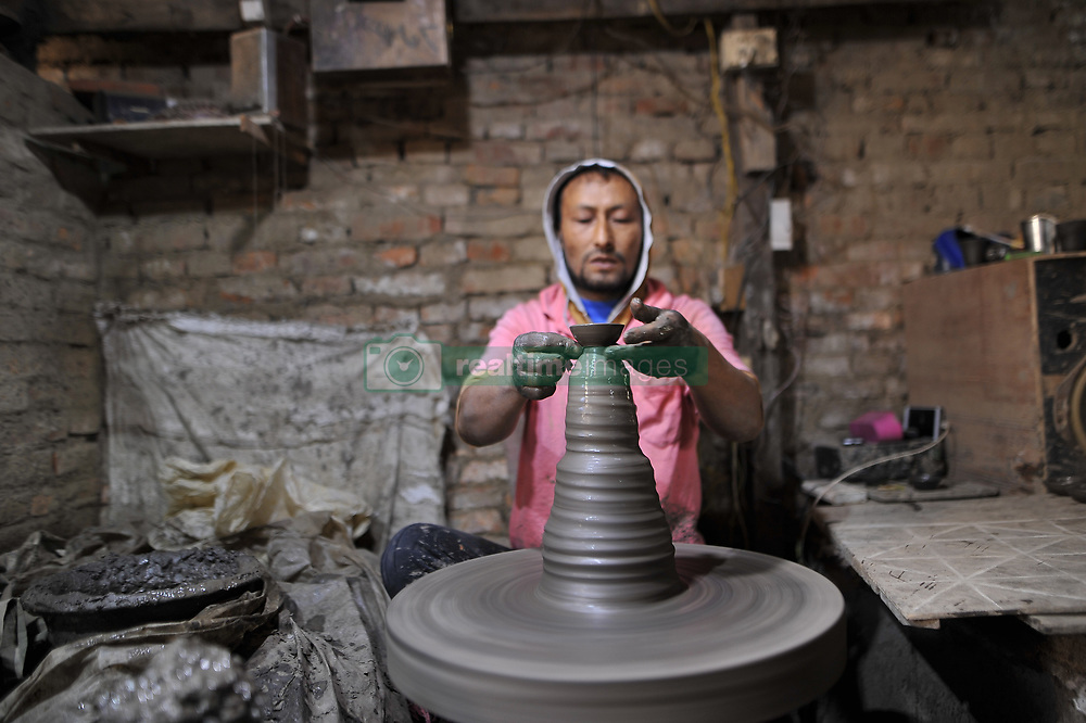 November 1, 2018 - Bhaktapur, NP, Nepal - 43yrs old SAHADEV PRAJAPATI, making clay pot lamps for upcoming Tihar or Deepawali Festival on his workshop at Pottery Square, Bhaktapur, Nepal on Thursday, November 01, 2018. Nepalese Potter works on their small scale traditional pottery making industry in Bhaktapur, Nepal. Bhaktapur is an ancient town in the Kathmandu Valley and is listed as a World Heritage Site by UNESCO for its rich culture, temples, and wood, metal and stone artwork. (Credit Image: © Narayan Maharjan/NurPhoto via ZUMA Press)