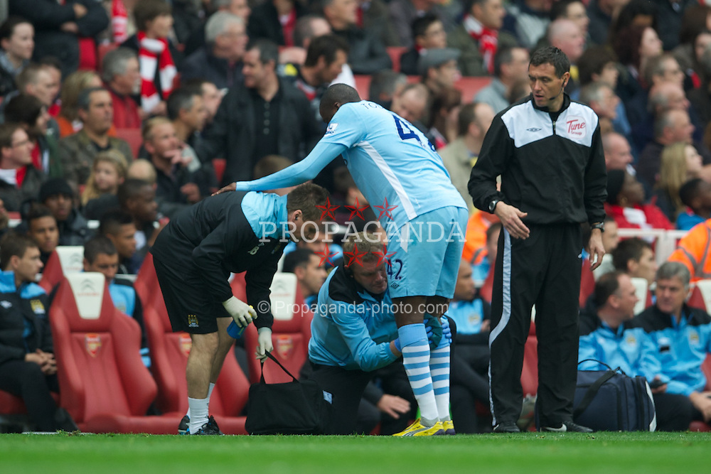 LONDON, ENGLAND - Easter Sunday, April 8, 2012: Manchester City's Yaya Toure receives treatment to his injured knee against Arsenal Song Billong during the Premiership match at the Emirates Stadium. (Pic by David Rawcliffe/Propaganda)