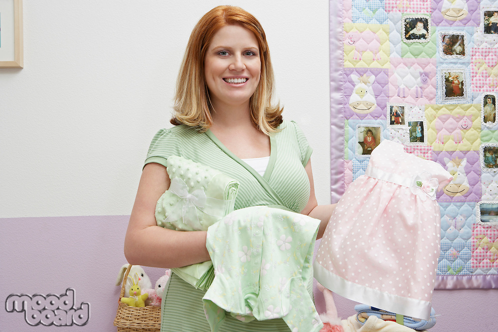 Pregnant woman standing in room, holding baby clothes